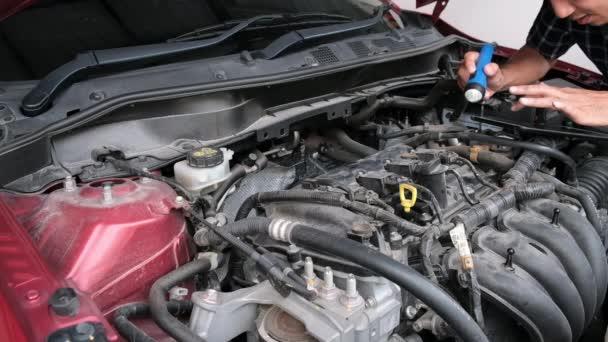 Asijský člověk mechanik inspekce Shine a baterka auto motor kontrola chyba v motoru z aplikace smartphone.Red auto pro servisní údržbu pojištění s motorem auta.for dopravy automobil automobilový automobil auto opravy