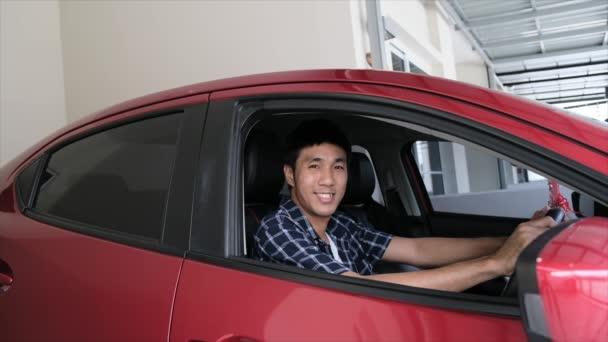 Asiat öffnet rote Autotür mit schlüssellosem Smart