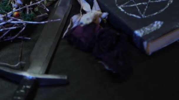 Hladký pohyb fotoaparátu a změna zaměření. Detailní záběr dýky na stůl a černou knihu s pentagramem. Koncept čarodějnického stolu pro rituály v předvečer Halloweenu.