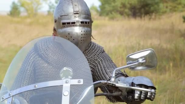 A medieval knight in full armor sits on a motorcycle against the backdrop of the forest.