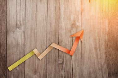 GROWING GRAPH LINE  BUSINESS PAPER ARROW ON WOODEN BACKGROUND