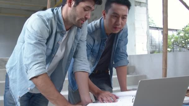 Stavební inženýři, inspektor a asijský architekt diskutují, setkávají se, kontrolují a radí o stavbě nebo rekonstrukci domu s plánem na staveništi. Koncept inženýrství.