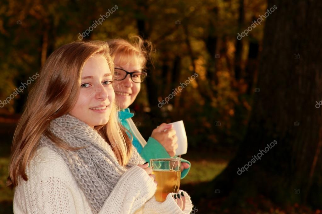 Daughter and mother drink tea in autumn park