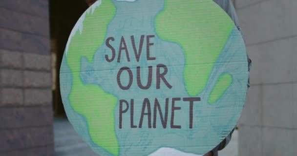 Közelkép az afro-amerikai emberről, aki a Föld modelljét írja, hogy megmentse a bolygónkat. Férfi kéz fogja a plakátot, miközben fellép a környezetszennyezés ellen. Az ökológia fogalma.