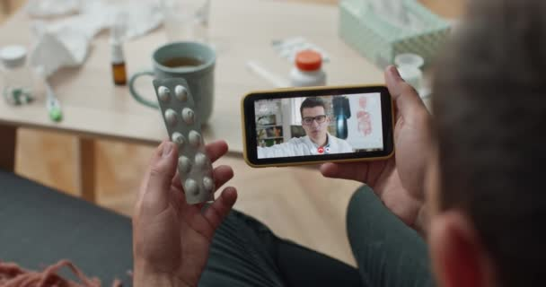 Over shoulder view of patient using video phone app for talking with male doctor at home. Sick man holding pill blister while having online consultation and sitting on couch.