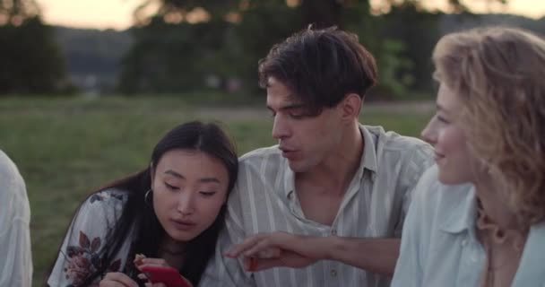 Young good looking man and woman looking at phone screen and talking while sitting on grass with friends. Millennial people having good time together at park. Concept of friendship.