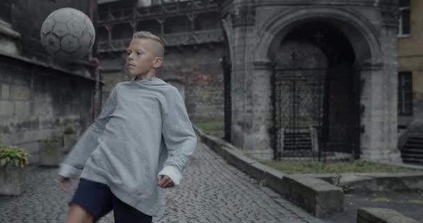Schnittansicht eines talentierten Teenagers, der Fußball mit dem Knie kickt. Junge Fußballspieler üben Tricks in der Altstadt. Konzept von Sport und Lifestyle.