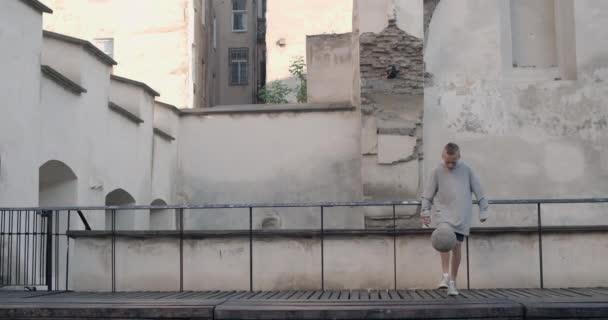Teenagerjunge hüpft Fußball mit Bein auf Dach des Altstadthauses Talentierte Kinder beim Üben und Trainieren von Fußballtricks. Konzept von Lebensstil, Kindheit, Sport.