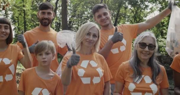 Großaufnahme von Freiwilligen in T-Shirts mit Recycling-Symbol, die lächeln und Daumen nach oben zeigen. Glückliche Menschen blicken in die Kamera, während sie Müllsäcke voller Müll in den Park halten.