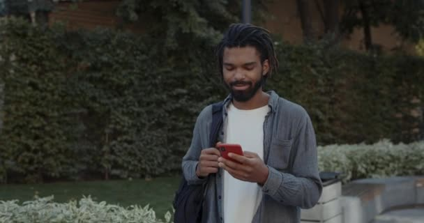 Crop view of cheerful young man with dreadlocks using smartphone and smiling. Happy bearded guy carrying bag on his shoulder and scrollingsocial media while walking at city street.