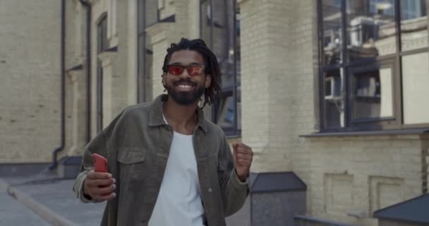 Joyful guy with dreadlocks smiling and dancing while looking to camera outdoors. Bearded afro american man in stylish red glasses having good mood and singing while walking at street.
