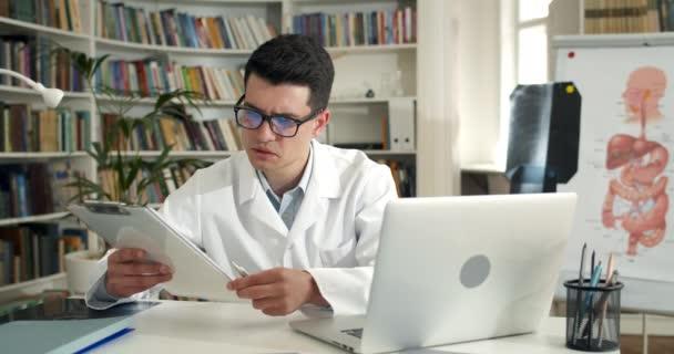 Mann im Gespräch und beim Betrachten medizinischer Dokumentation. Professionelle männliche Arzt in weiß rob mit Laptop für die Kommunikation mit Patienten während Videoanruf. Konzept der Telemedizin.
