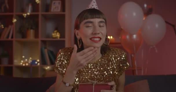Szülinapi kalapos nő vigyáz az ajándékra, miközben örül és kamerába néz. Millenniumi csinos nő ünnepel és csókokat fúj, miközben otthon ül. Az online fél fogalma.