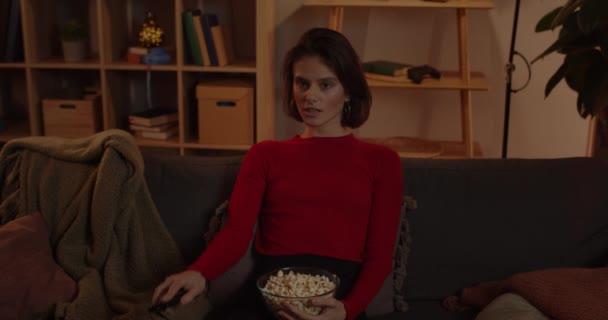 Schnittansicht von Millennial fröhliche Frau nimmt Fernbedienung und schaltet den Fernseher ein. Schöne weibliche Person, die Schüssel mit Popcorn hält, während sie gemütlich auf der Couch sitzt und Film guckt.
