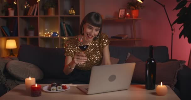 Positive young woman cheering to laptop screen with glass and drinking wine while talking. Charming female person in stylish clothes smiling while having video call and sitting on sofa.
