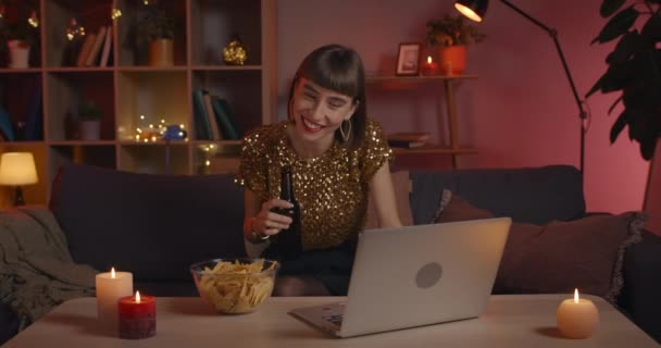 Positive young woman laughing and drinking beer from glass while looking at laptop screen. Positive female person in stylish clothes communicating online while sitting on couch.