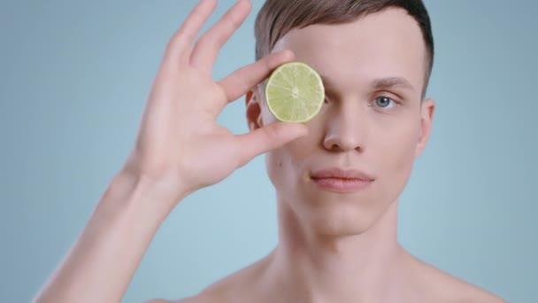 Egy jóképű férfi portréja, aki fél lime-ot tart a kezében, miközben a kamerába néz. Férfi fiatal modell csupasz vállak és világoskék szem pózol a gyümölcs.koncepció a bőr, egészségügyi ellátás.