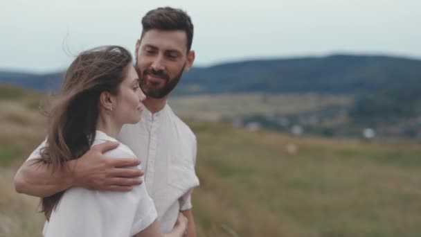 Couple standing in hugs on high hill and looking in distance