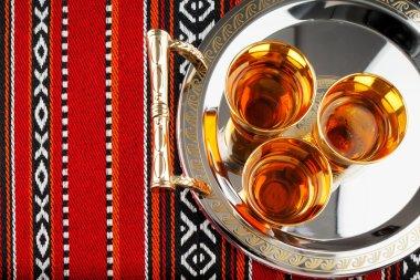 A tray of Arabian tea cups is placed on Arabian woven fabric