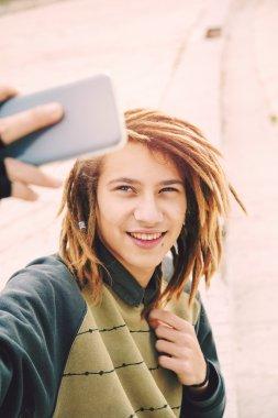 handsome rasta teen guy selfie in the city warm filter applied