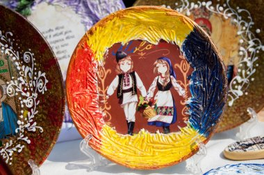 Plate where the background of the Moldovan flag, boy and girl bear with basket of flowers.