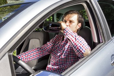 Young businesssman drinking alcohol while driving