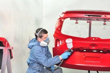Painter spraying red base.