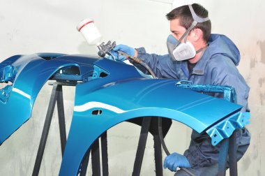 Worker painting blue bumper.