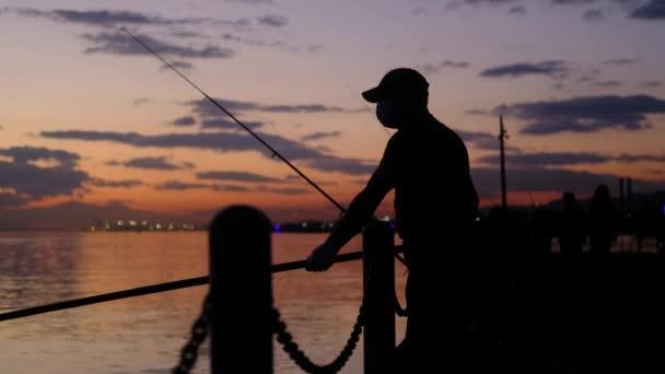 Zrzavá silueta muže rybařícího ve vzduchu