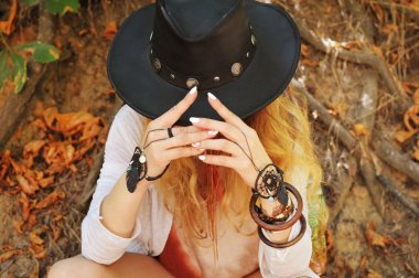Beautiful female hands with boho chic dreamcatcher bracelets and black leather hat