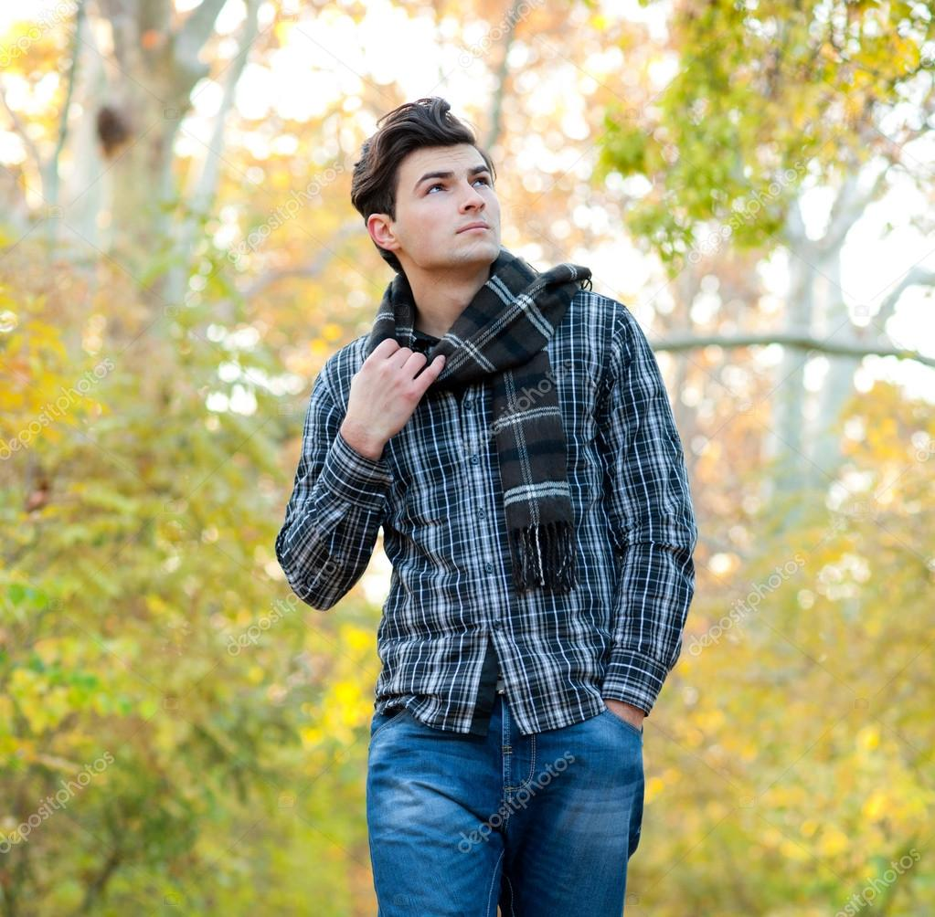Man dressed in a plaid scarf walking in autumn park.
