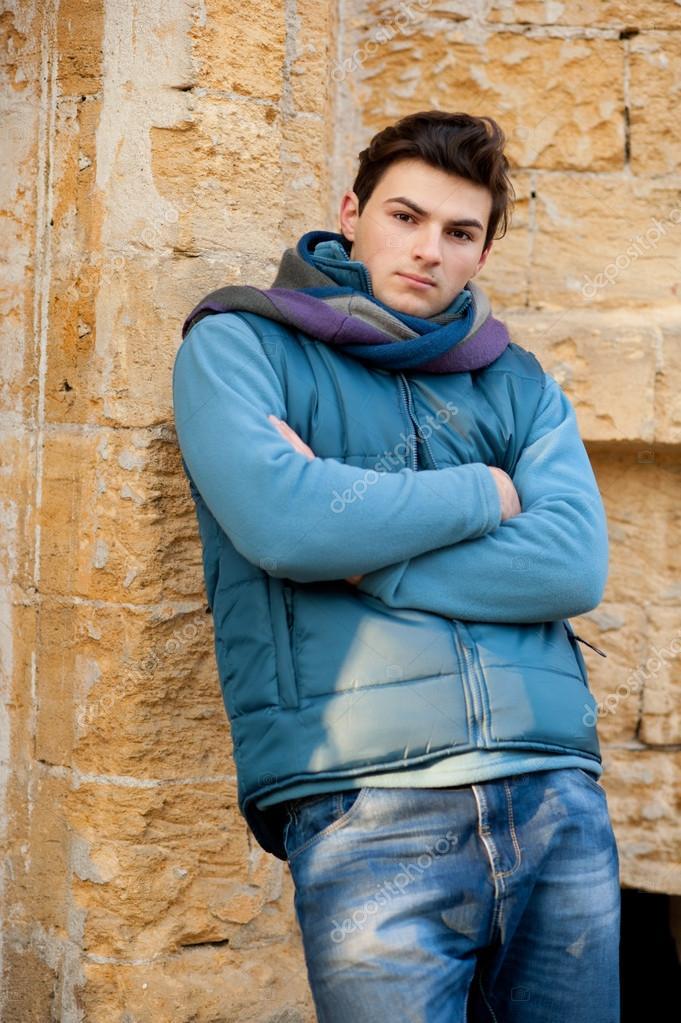 Portrait of a model man against urban wall.