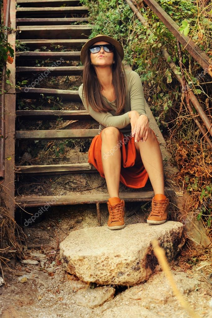 Funny Young Fashion Girl Sitting On The Old Wooden Stairs