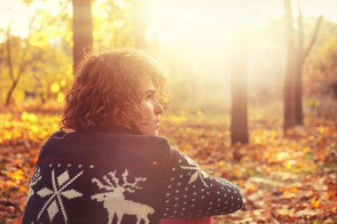 Man dressed in knit sweater with deers sitting  on autumn leaves in park.