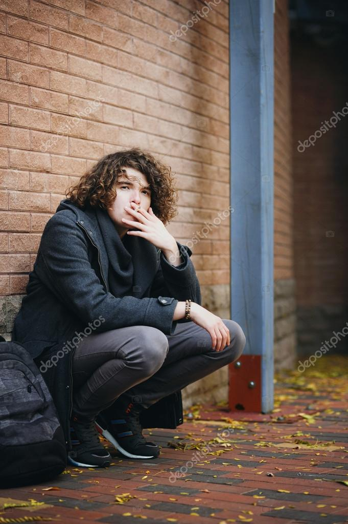 Portrait of a handsome man standing against brick wall and smoki