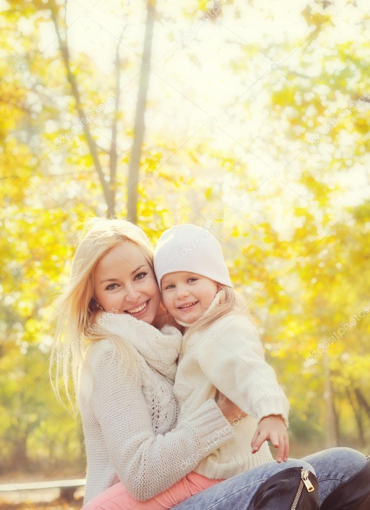 Portrait of a happy family with beautiful blonde mother and little daughter resting in park.