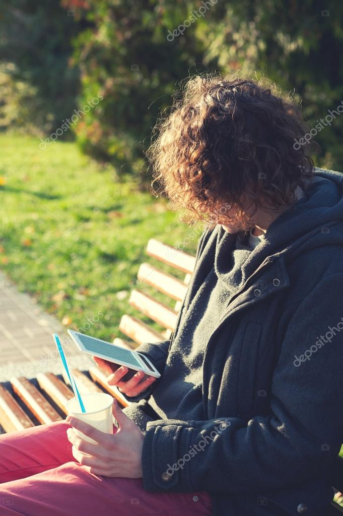 Man sitting in autumn park on a bench, reading the electronic book and drink some coffee.