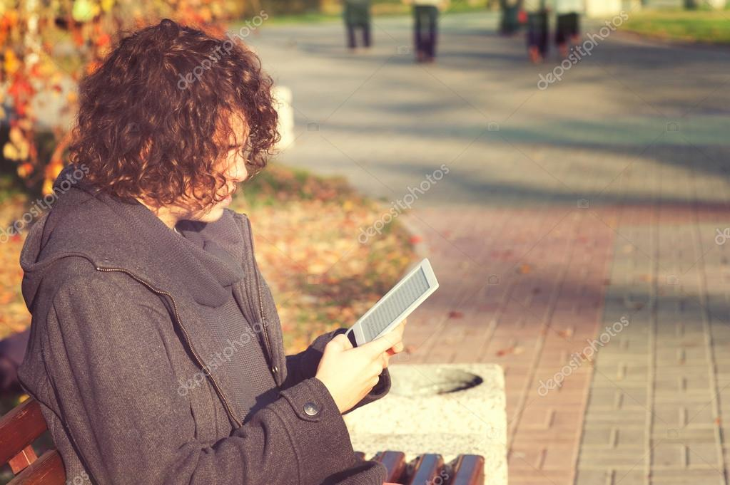 Young man sitting in autumn park and read the electronic book.