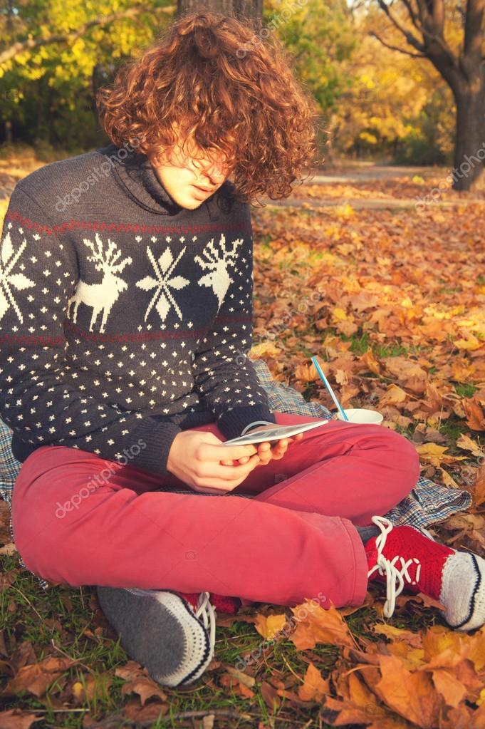 Young adult man sitting in autumn park and reading the electronic book.