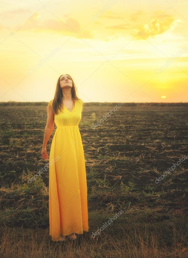 Cute young woman relaxed breathing fresh air, standing  with closed eyes.