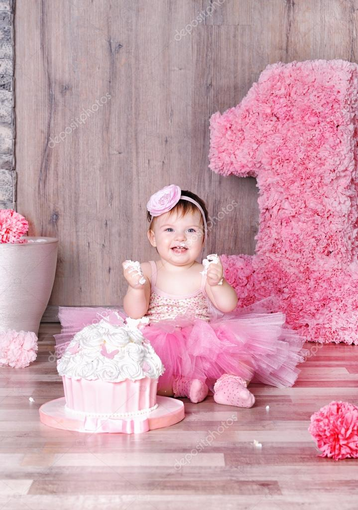 Cute baby girl eating first birthday cake Stock Photo slena