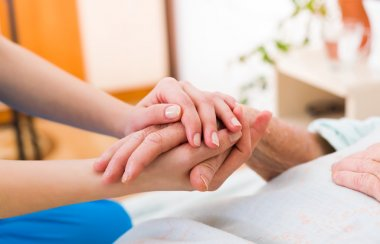 Nurse holding the hand of an elderly woman