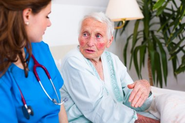 Kind nurse listening to senior sick woman