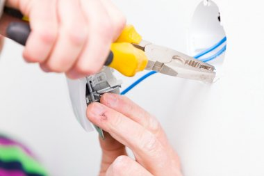 Electrician using tools for installing light