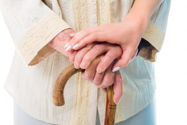 Elderly woman's hands held by a consoling hand