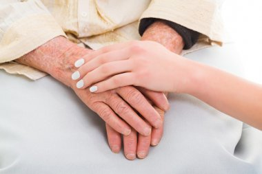 Elderly hands held by a young person