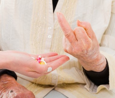 Elderly woman refusing medications with a rude gesture
