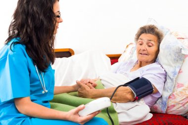 nurse using digital blood pressure measure