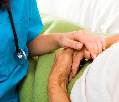 nurse holding elderly lady's hand