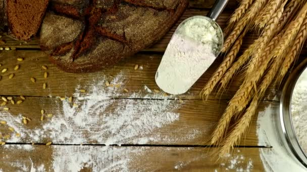 Bread, sheaf of wheat ears and flour  on a wooden table, dolly, top view